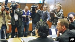 Rami Makanesi, foreground left, awaits the beginning of his trial at a court in Frankfurt, Germany, May 5, 2011