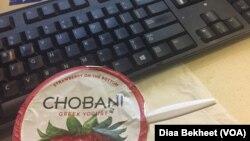 A Chobani yogurt cup is displayed next to a computer keyboard at VOA newsroom, Nov.28, 2017. (Photo: Diaa Bekheet)