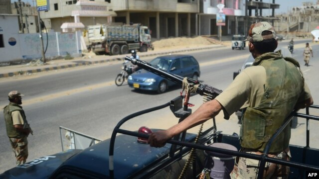 Pakistani paramilitary soldiers stand guard on a street ahead of the upcoming parliamentary elections, in Karachi on May 9, 2013.