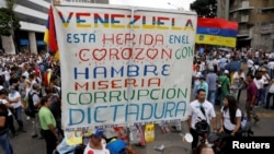 "FILE - Opposition supporters rally against President Nicolas Maduro carrying a sign that reads ""Venezuela is wounded in the heart with hunger, misery, corruption and dictatorship"", in Caracas, Venezuela, May 10, 2017."