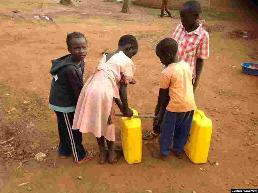 South Sudanese children at Kiryandongo settlement camp in northern Uganda struggle to carry full jerry cans of water.