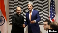 U.S. Secretary of State John Kerry shakes hands with Anil Madhav Dave, India's minister of environment, forest and climate change, before holding a bilateral meeting to promote U.S. climate and environmental goals at the Meeting of the Parties to the Montreal Protocol on the elimination of hydro fluorocarbons use in Rwanda's capital Kigali, Oct. 14, 2016.