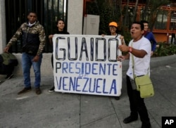 """FILE - Anti-government protesters show a sign reading in Spanish """"Guaido, President of Venezuela"""" after a rally demanding the resignation of President Nicolas Maduro in Caracas, Jan. 23, 2019."""