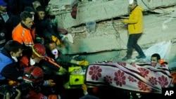 Tim SAR membawa seorang perempuan yang berhasil diselamatkan dari reruntuhan bangunan delapan tingkat yang roboh di Istanbul, Turki, 6 Februari 2019.