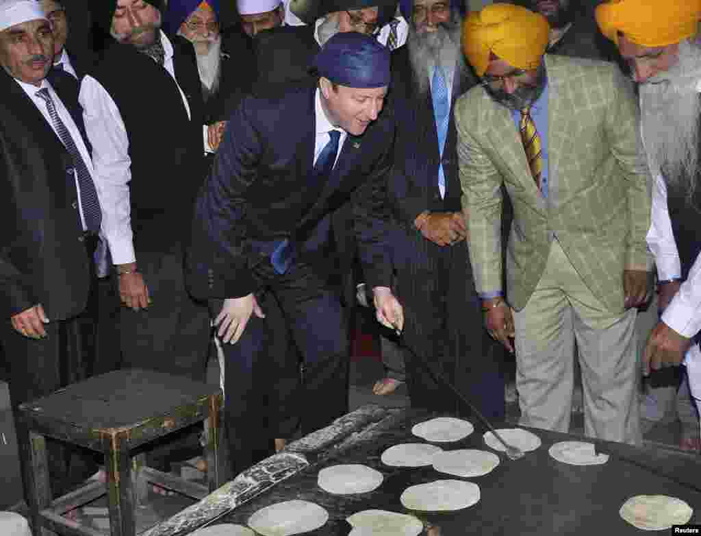 Britain's Prime Minister David Cameron (C) prepares bread at a community kitchen during his visit to the holy Sikh shrine of Golden temple in the northern Indian city of Amritsar.