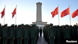 FILE - Paramilitary policemen stand in formation as they pay tribute to the Monument to the People's Heroes on Tiananmen Square in Beijing, November 2013.
