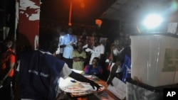 Electoral officials count ballot papers under a lantern light at the end of voting at a polling station in Monrovia, Liberia, Oct. 10, 2017.