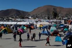 FILE - Migrants walk inside a former concert venue serving as a shelter in Tijuana, Mexico, Dec. 3, 2018.