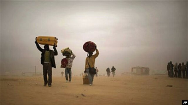 Men, who used to work in Libya and fled the unrest in the country, carry their belongings as they walk during a sand storm in a refugee camp at the Tunisia-Libyan border, in Ras Ajdir, Tunisia, March 15, 2011