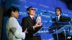 """中国盲人法律活动人士陈光诚在纽约""""人权第一""""晚宴上接受""""人权奖"""",影星克里斯汀·贝尔(右)站在他身边。 (2012年10月24日)"""