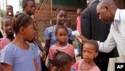 지난 19일 아프리카 기니에서 의료 요원이 등교하는 학생들의 체온을 측정하고 있다.