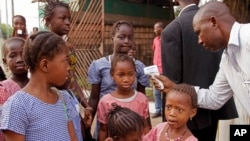 Un trabajador de la salud toma la temperatura a escolares en busca de síntomas de ébola, antes de que ingrersen a clase, en Conakry, Guinea.