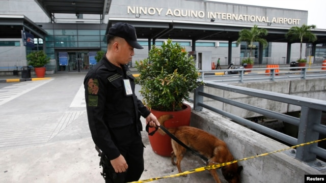 An airport police officer and a sniffer dog patrol Terminal 3 of the Ninoy Aquino International Airport in metro Manila, Sept. 1, 2014.