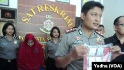 Polisi menunjukkan rentengan keping emas dalam plastik hasil sitaan kasus investasi emas ilegal. (Foto:VOA/Yudha)