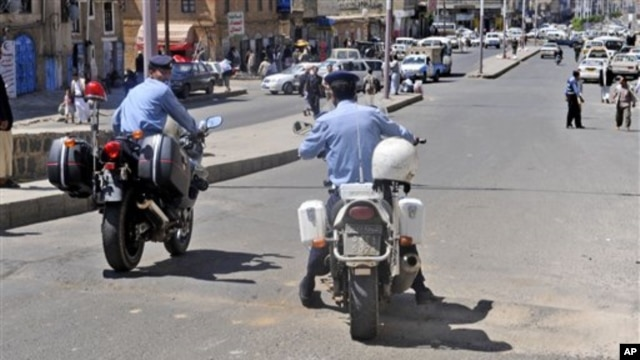 Yemeni policemen attend the scene where an attack took place on a convoy carrying a senior British diplomat in San'a, Yemen, 6 Oct 2010