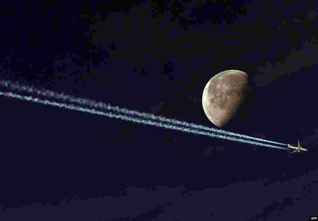 A jetliner leave a vapour trail as it passes in front of the moon in this photo taken from the Algerian capital Algiers.