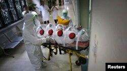 Медики в защитных костюмах перевозят манекен, иммитирующий больного лихорадкой Эбола, в спецблок в ходе учений в одной из больниц КНР. 16 октября 2014 г.