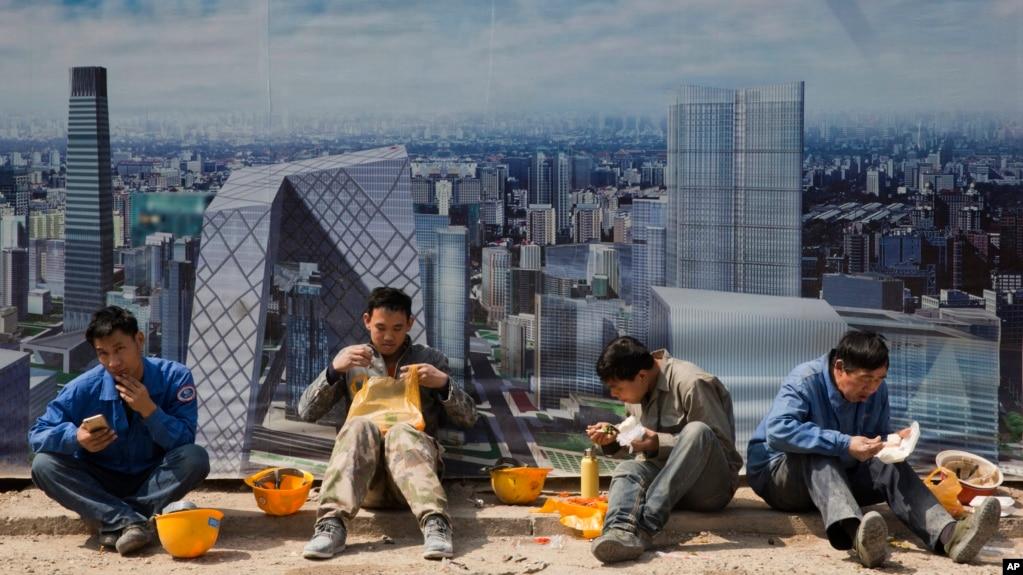 北京一个建筑工地外面,工人吃午饭,旁边的板子上有中央商务区的影像