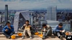 Pekerja konstruksi makan siang dekat sebuah gambar Pusat Distrik Bisnis di luar sebuah lokasi konstruksi di Beijing, China, 6 April 2017.