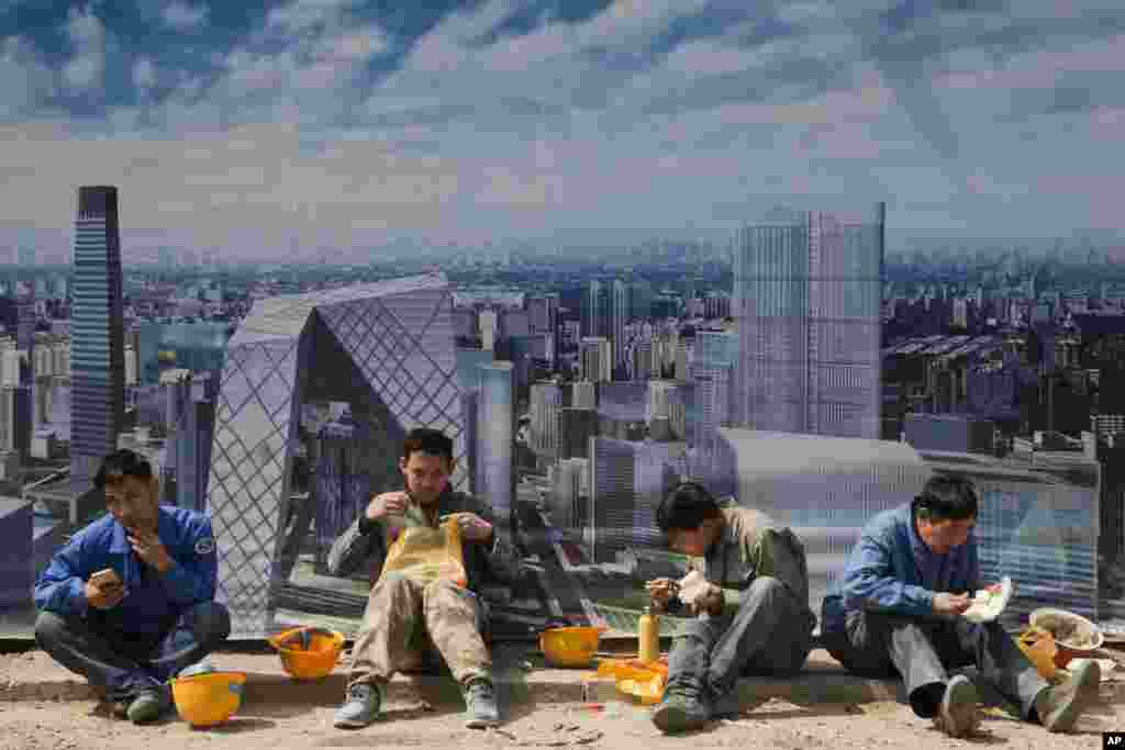 Construction workers eat lunch near a board with an artist's impression of the central business district, outside a construction site in Beijing, China.