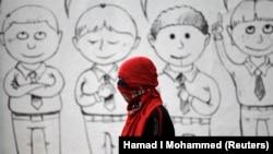 Seorang berdiri di depan mural siswa sekolah di dinding sekolah menengah untuk menentang hukuman mati otoritas Saudi. (Photo: REUTERS/Hamad I Mohammed)
