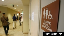 FILE - A sign marks the entrance to a gender neutral restroom at the University of Vermont in Burlington, Vermont.
