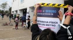 Una mujer sostiene un cartel que llama a mantener el distanciamiento social en un centro de votación en Santiago, Chile, durante un referendo para decidir si se cambia la constitución. Domingo 25 de octubre de 2020.
