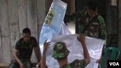Personel TNI yang disiagakan di desa Tangkura sedang memeriksa peta Kecamatan Poso Pesisir Selatan, Senin 26/1 (foto: VOA/Yoanes).