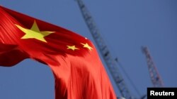 China's national flag is seen in front of cranes on a construction site at a commercial district in Beijing, China, Jan. 26, 2016.