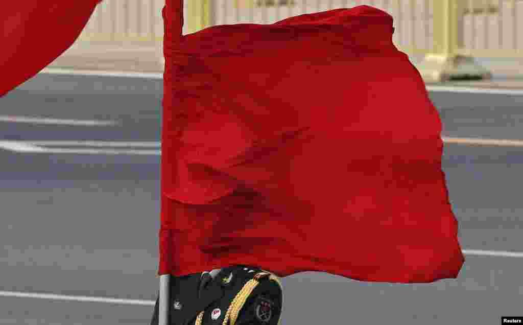 Gió thổi là cờ che khuất mặt người lính trong hàng quân danh dự trong buổi lễ đón Thủ tướng Australia Julia Gillard bên ngoài Đại sảnh Nhân dân ở Bắc Kinh, Trung Quốc.