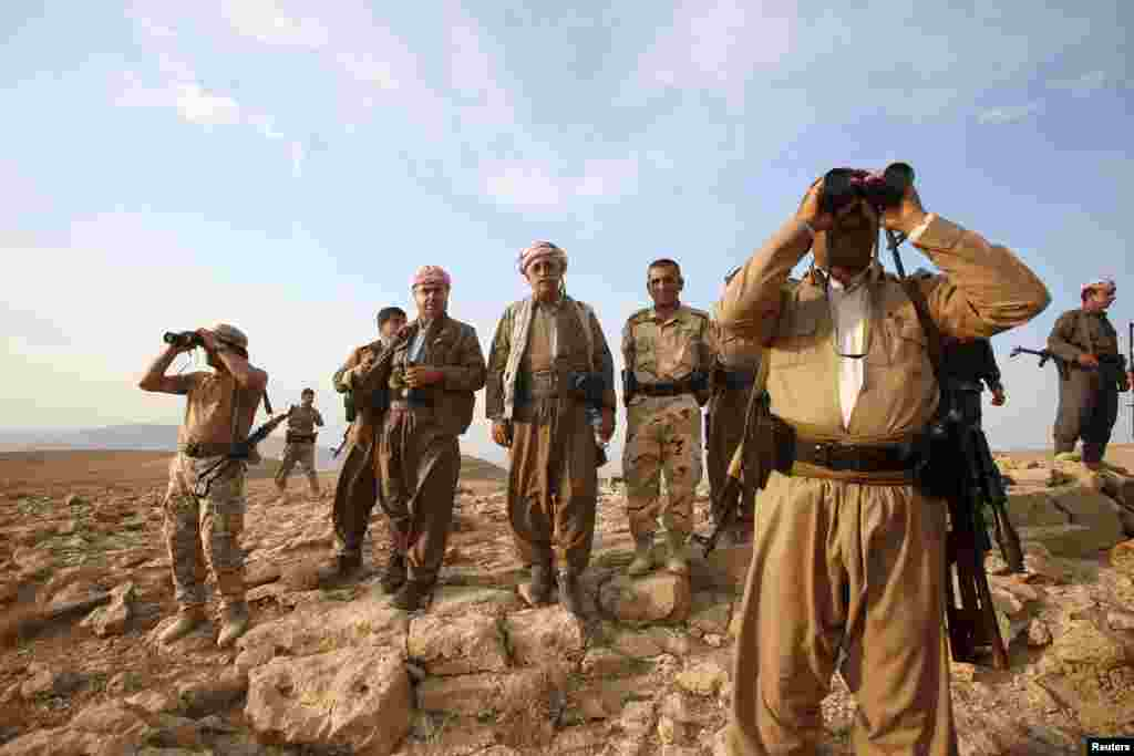 Kurdish Peshmerga forces stand guard near the town of Makhmur, south of Irbil, after the Islamic State militants withdrawal, Aug. 18, 2014.