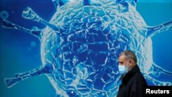 A man wearing a protective face mask walks past an illustration of a virus outside a regional science centre. REUTERS/Phil Noble
