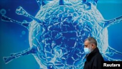 A man wearing a protective face mask walks past an illustration of a virus outside a regional science centre. (REUTERS/Phil Noble)