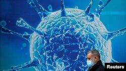Seorang pria memakai masker, berjalan melewati ilustrasi virus COVID-19 di luar pusat sains regional di Oldham, Inggris, 3 Agustus 2020. (REUTERS / Phil Noble).