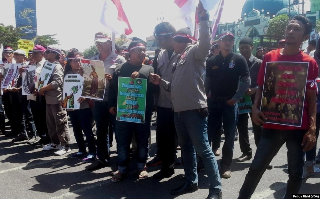 """数十名抗议者在印尼东爪哇省首府泗水的省议会大楼前集会抗议,要求拆除图班市(Tuban)关胜庙竖起的一座关公像(2017年8月7日)。抗议者称,30米高的关公像与印尼民族文化不符。一些反对人士认为,关公像表明华人控制了印尼政府,也有人说,雕像没有获得必要的建设许可。寺庙用一块白布将关公像遮罩起来。 印尼最大的穆斯林组织之一伊斯兰反歧视网络的活动人士阿安·安所里称,反对关公像是由""""伊斯兰国""""组织的一个当地分支操控的,他们试图通过联合其他思想上不宽容的组织来建立自己的基本盘。"""