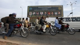 People ride motorcycles past a banner promoting the Eighth D-8 Summit in Islamabad November 21, 2012.