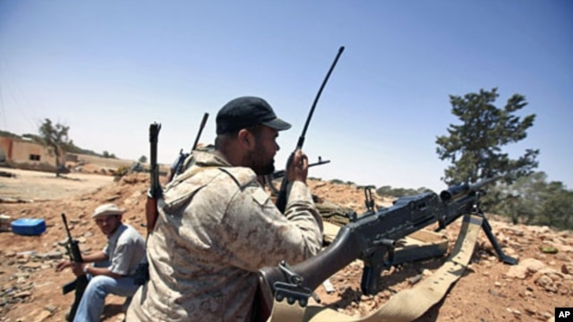 A Libyan rebel fighter uses a walkie talkie at their position in Misrata's western front line, some 25 km (16 miles) from the city center June 9, 2011