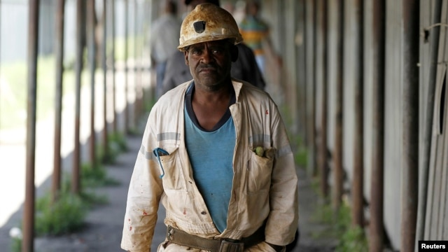 Miners walk at the end of their shift at the Anglo Platinum's Khuseleka shaft 1 mine in Rustenburg, northwest of Johannesburg, January 15, 2013.