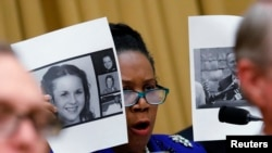 Rep. Sheila Jackson Lee (D-TX) holds up pictures of women who've accused U.S. Senate candidate Roy Moore of sexual misconduct, while questioning U.S. Attorney General Jeff Sessions (not pictured) during the House Judiciary Committee oversight hearing on Capitol Hill in Washington, Nov. 14, 2017.