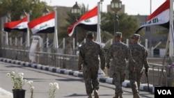 Banderas iraquíes en el Campo Victoria donde soldados estadounidense caminan a la salida del palacio Al Faw.