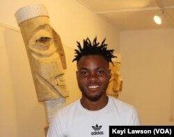 Atisso Goha, un artiste togolais qui sculpte en bois des œuvres géantes, à Lomé, Togo, le 19 avril 2019. (VOA/Kayi Lawson)