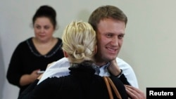 Russian opposition leader Alexei Navalny embraces his wife Yulia after the announcement of the verdict, Oct. 16, 2013.