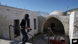Un jeune au visage masqué marche dans la tombe de Joseph lors des affrontements avec les troupes israéliennes, près de Naplouse, en Cisjordanie, 24 avril 2011.