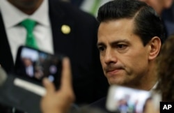 Invited guests take cell phone pictures of Mexico's President Enrique Pena Nieto following his address in response to the U.S. presidential election in Mexico City, Wednesday, Nov. 9, 2016.