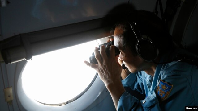 Military officer Pham Tuan Minh looks through a window of a Vietnam Air Force AN-26 aircraft during a mission to find the missing Malaysia Airlines flight MH370, off Con Dao island March 13, 2014.