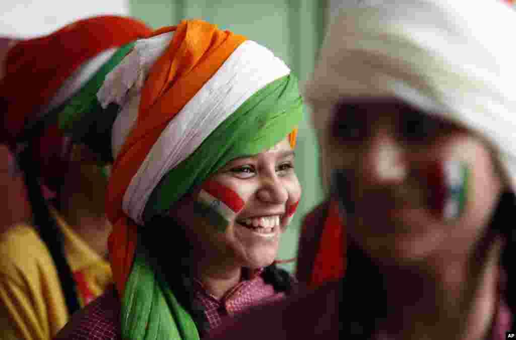 Seorang gadis, dengan wajah yang dilukis dengan tiga warga bendera India, tersenyum saat menanti giliran tampil dalam pertunjukan sekolah sehari sebelum perayaan hari kemerdekaan India di Jammu. India merayakan kemerdekaannya dari Inggris yang diraih tahun 1947 hari Sabtu (15/8).