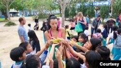Phát kẹo bánh cho các em học sinh. (Hình: Hugh Bohane)