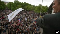 A pro-Russian activist waves a Donbas Republic flag over a crowd celebrating the capture of an administration building in the center of Luhansk, Ukraine, one of the largest cities in Ukraine's troubled east, April 29, 2014, as demonstrators demand greater autonomy for Ukraine's regions.