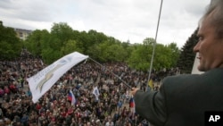 FILE - A Pro-Russian activist waves a Donbas Republic flag over a crowd celebrating the capture of an administration building in the center of Luhansk, Ukraine, one of the largest cities in Ukraine's troubled east, April 29, 2014.