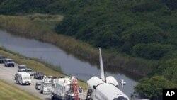 Atlantis remorqué en direction d'un hangar de garage